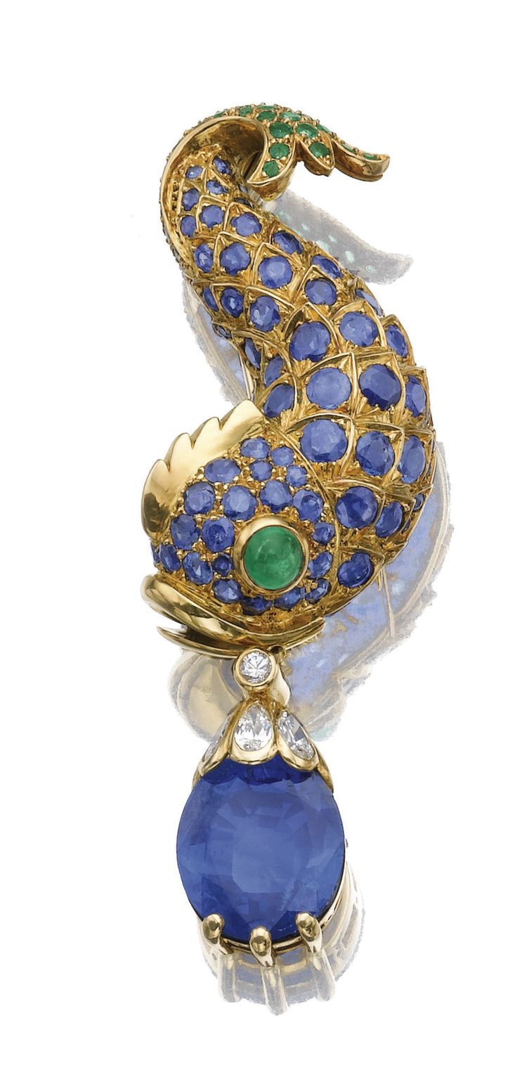 GEM-SET AND DIAMOND BROOCH, RENÉ BOIVIN, CIRCA 1960. Designed as a dolphin set with a cabochon emerald and circular-cut sapphires and emeralds, suspending an oval sapphire drop with a surmount of pear-shaped and brilliant-cut diamonds.