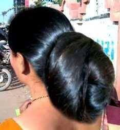 Extremely large low bun. Care however should be taken before adopting such hairstyles, as due to it's high static charge, it will cause phlegm to move up in the throat, causing the voice to quaver & a frequent urge to clear the throat. A heavy chabi chhalla with a long & wide hook if inserted at the edge of the pleats of the saree, will reduce this problem as it's hook will activate the acupressure points that act to keep the throat clear.