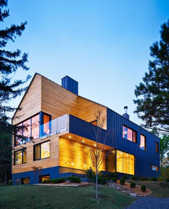 """Rezidence """"La Grange"""" se nachází v nádherné kanadské oblasti Charlevoix s úchvatným výhledem na řeku svatého Vavřince. Umístěná je na hřebeni svahu a je obklopená lesem. Architektura tohoto impozantního dvoupodlažního domu vychází z drsného kouzla daného místa, které se promítá do strohého zpracování."""