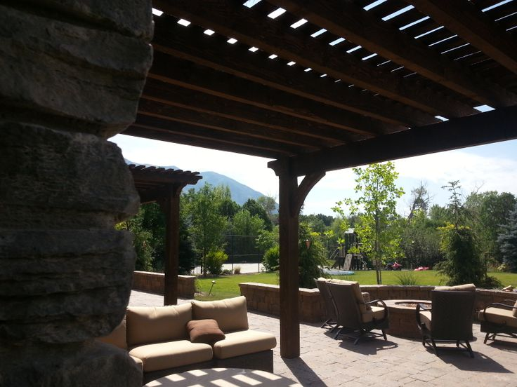 Pergola and a outside paver fire pit by the swimming pool in Alpine Utah