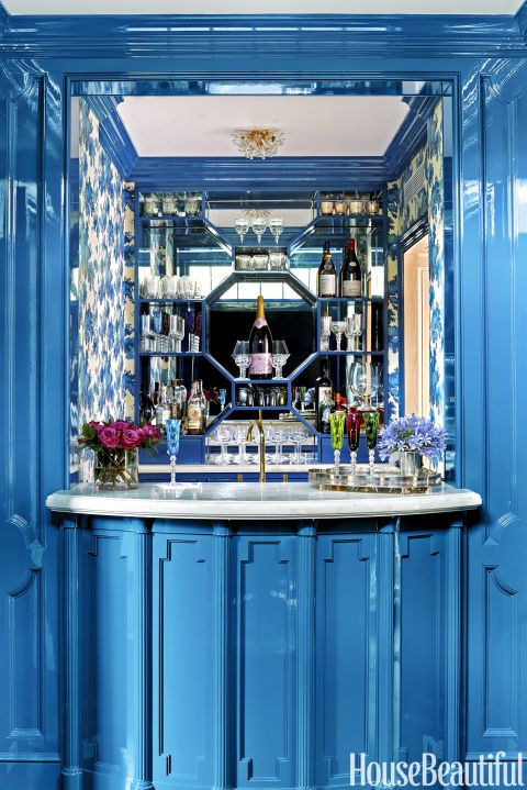 """The mirrored bar — lacquered in Benjamin Moore's Summer Nights, embellished with Sandberg's Raphaël wallpaper, and topped with a white-onyx counter — """"is a little jewel-box moment,"""" McCarthy says."""