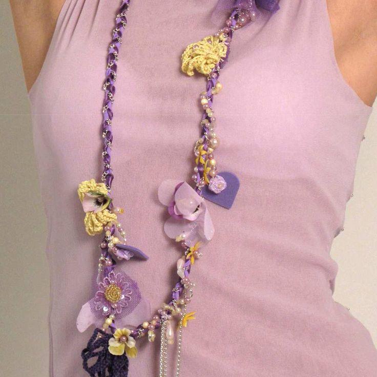 Questa collana ispirata al tema dei fiori  e' tutta realizzata a mano, i fiori sono fatti all'uncinetto in filato lino-cotone e ricamati a mano con perle, paillettes e materiali in resina. La caten...