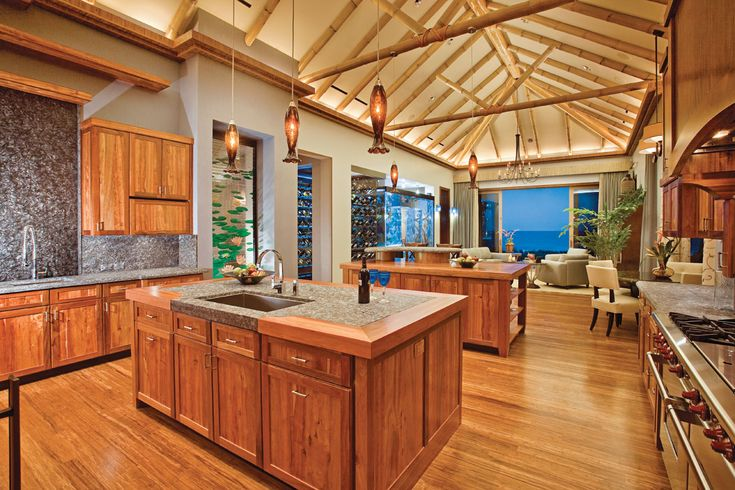 Bamboo ceiling beams shape this oceanfront kitchen fashioned with Hawaiian Koa wood, granite countertops with ruby red aggregates and silver mica flecks, and a double-sided 10-foot kitchen water wall. Just beyond is a matching catering kitchen.