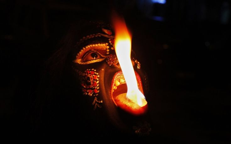 an Indian performer disguised as Hindu Goddess Kali performs with fire during Navratri festival in Allahabad, India. Navratri or the festival of nine nights is an annual Hindu festival of worship and dance. (AP Photo/Rajesh Kumar Singh)
