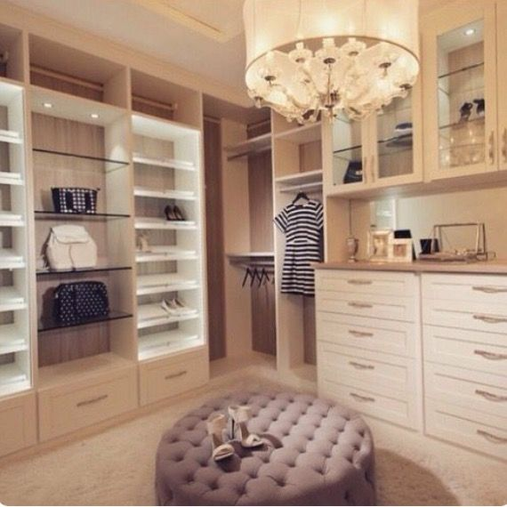 Walk in closet to dream about. Love the display area for bags and shoes. And the round upholstered ottoman in the middle of the closet.