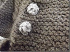 The crocheted button. Chain 12. Turn. Single crochet in each chain. Fasten off and break the yarn. Roll up the little strip you just made and sew it together and at the bottom. Tie the ends together, and then use them to sew it to your sweater