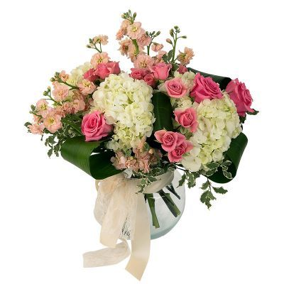 Gentle Wishes - Soft, fluffy hydrangea with fragrant peach-coloured stock and pink spray roses. All designed in a recycled glass vase, which is decorated with lace and satin. Feminine, indeed!