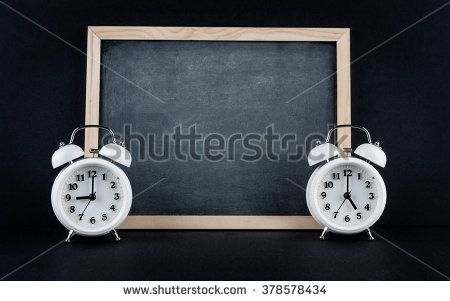 Two vintage alarm clocks showing 9 and 5 o'clock with empty chalkboard on black background. Nine to five corporate working hours concept.