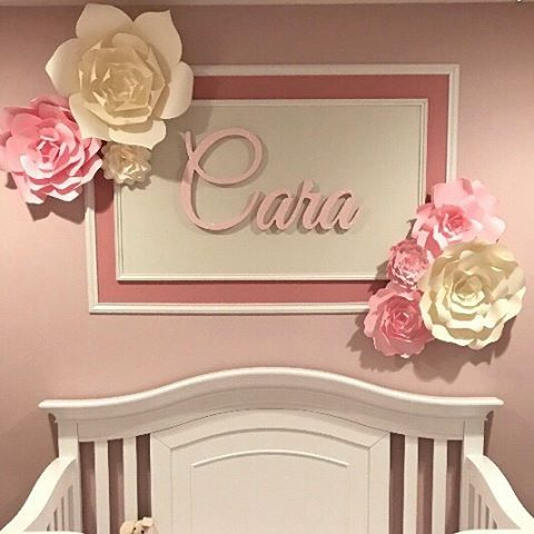 Paper flower nursery decor. These large pink paper flowers make a stunning feature wall in this adorable little girls nursery. www.paperflower.com