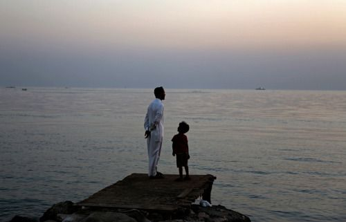 A Bahraini man and his son look for the new moon that marks the start of the Islamic holy month of Ramadan along the Persian Gulf coast, in Karzakan, Bahrain, on June 5, 2016.  Hasan Jamali