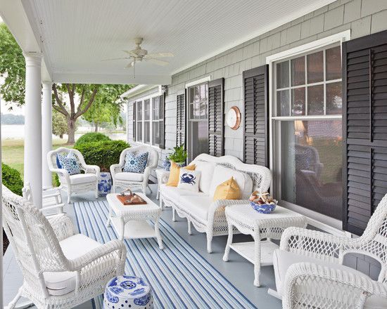 Southern style front porch with white wicker furniture, blue chinoise pillows and nautical decor.  Love the blue rug and shutters!