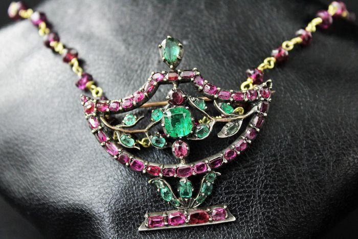 Online veilinghuis Catawiki: Ketting / broche in goud, met smaragden en robijnen.