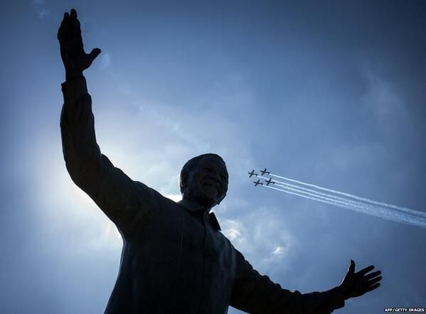 Air force jets fly over Nelson Mandela statue to mark 20 years since the end of apartheid in South Africa. [Photo via BBC]