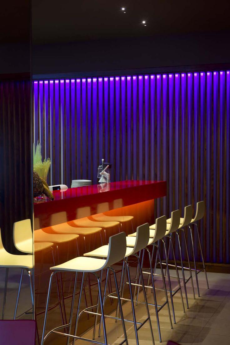 La encimera de la barra es de Silestone Rosso Monza y la parte frontal de placas de vidrio pintadas a alta temperatura de color naranja.