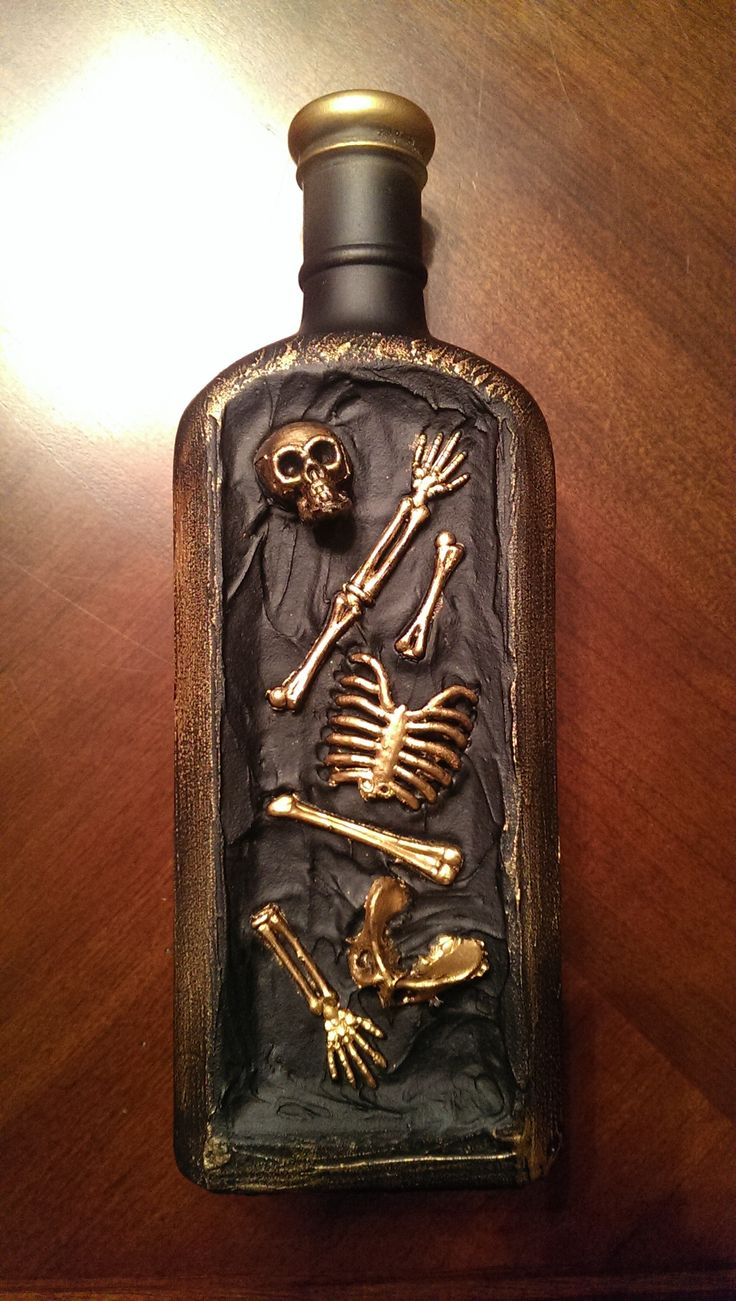 Altered bottle for Halloween.  Was an old glass bottle.  used a plastic skeleton from the dollar store, tore it apart.  Put a thick layer of modeling paste onto front of bottle and applied the pieces.  once dry, spray painted black and used rub and buff gold to antique it