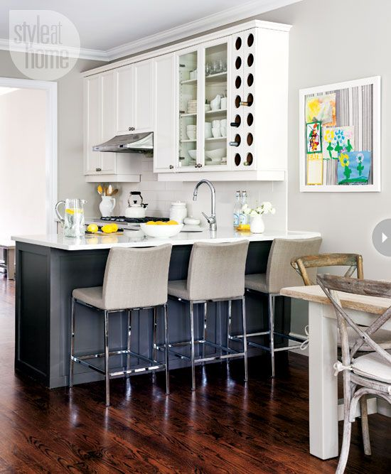 The dining room side of the kitchen peninsula was painted grey to add contrast and disguise dings and spills from three kids eating meals there. Tight-fitting slipcovers on the bar stools are a practical choice as well.