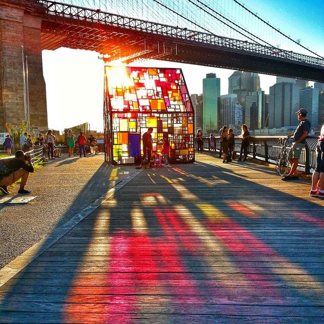 Check out those rainbow reflections! For this year's DUMBO Arts Festival, artist Tom Fruin and performance duo CoreAct presented a collaborative project called Reflection / Kolonihavehus in Brooklyn Bridge Park. Fruin's colorful plexiglass house, called Kolonihavehus, was on display. In previous years, the outdoor sculpture had been shown throughout Europe, such as in Sweden, Denmark, Austria and the Czech Republic. New York had already seen one of Fruin's pieces, the monumental sculpture…