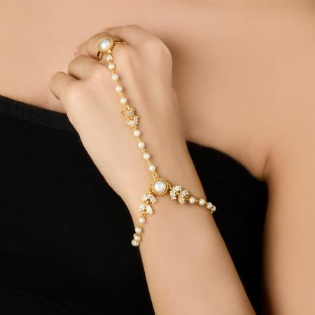 Elegant pearl and diamond finger bracelet is garnished with pearl in the center of the bracelet. Diamonds in the sides which is attached with the pearl chain and ring is also attached with the pearl and diamond chain. This elegant finger bracelet you can match with any of your traditional outfit. #BeautifulRingBracelet