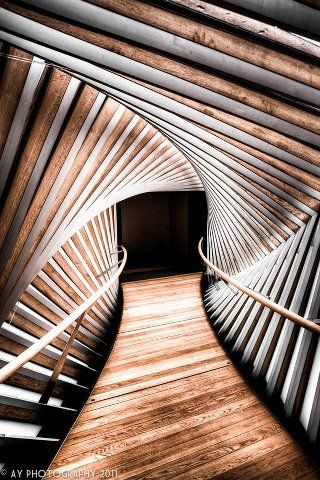 The Bridge of Aspiration at the Royal Ballet School in London Photographer: Unkown The twisted structure of the bridge in this photograph is reminiscent of a DNA helix. The wooden slats create an energetic force that leads to a black space, guided in by the wooden hand-rails on either side.