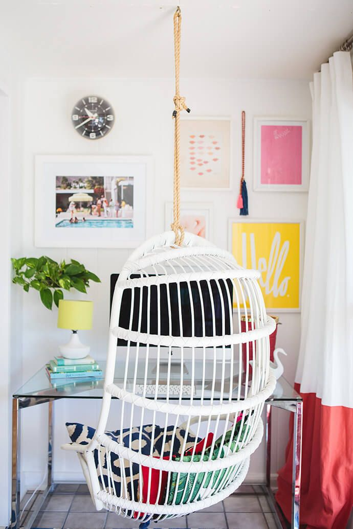 Boho chic office space with a bright gallery wall and a hanging chair