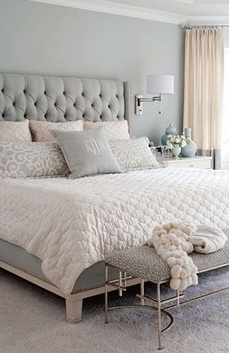 Bedroom decor ideas - Transitional style, light grey, cream and white color palette. Tufted headboard, bench, drum wall sconces above side tables and full length cream curtains.