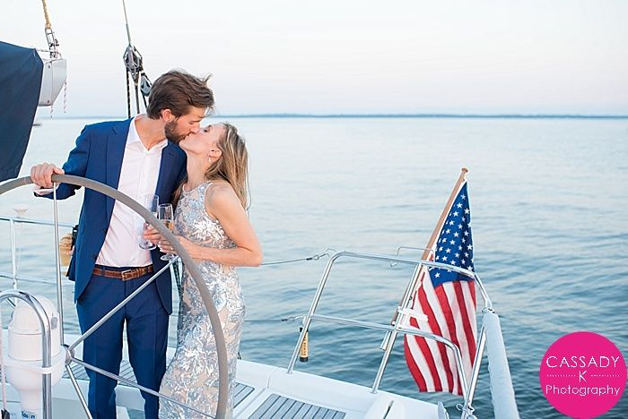 Nautical Sunset Engagement Session on a Sailboat at the American Yacht Club, Rye, NY. With Champagne, an American Flag & a Sequin Dress - Cassady K Photography