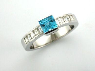 'EMILY' --  Swiss Blue Topaz Engagement Ring  set with Square Cut Topaz  & Baguette Cut Diamond Channel Set along the Shoulder  in 18ct White Gold  Diamond Wt. -  0.45 carat.