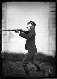 WHERE have I seen this?  Glass plate negative (1 of 193), portrait of boy wearing a mask holding a rifle, glass, photographer possibly Arthur Phillips, Australia, c. 1895-1905 - Powerhouse Museum Collection