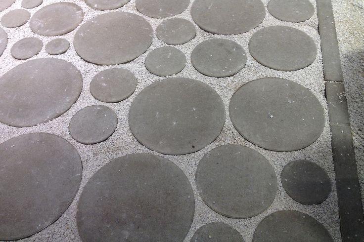 Grote betontegels met split of gras tussen de cirkels, geschikt voor een oprit. Aviena Circle van www.ebema.nl.