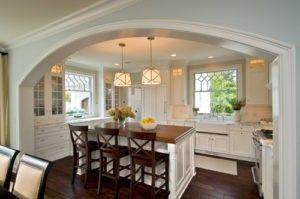 Dies ist ein weiteres Beispiel eines Bauernhauses inspirierte Küche Idee mit weißen gewölbten Eingangsbereich mit Formteil. Eigenschaften umfassen Glas Schränke, ein Bauernhaus sinken und Holz-Arbeitsplatten. Es gibt auch eine weiße und braune Kücheinsel hosting mit drei Holzstühlen. Die Farbe der Hartholz-Fußböden verschmelzen mit der braunen und weißen Design der Küche. Foto von Witt Bau mehr traditionelle Küche Ideen