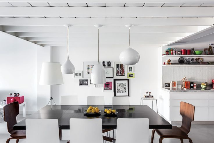 Sobre la mesa (Eugenio Aguirre) rodeada de sillas blancas (Restoration Hardware) y marrones (West Elm) cuelgan tres lámparas de techo (Crate & Barrel). Las sillas rojas (Design Within Reach), por su parte, arman un escritorio debajo del volumen del entrepiso.  /Daniel Karp