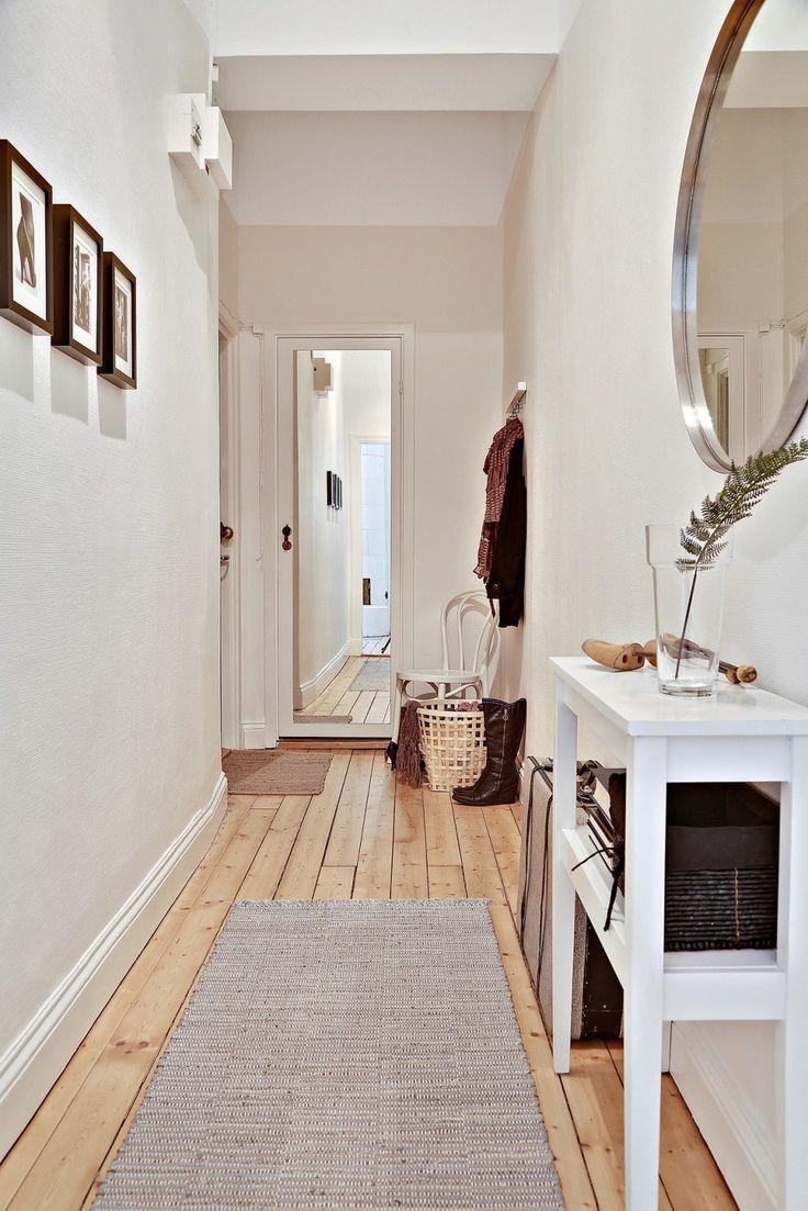 Couloir d'entrée d'un appartement. Blanc, bois. Cadres sur un mur, miroir sur l'autre mur