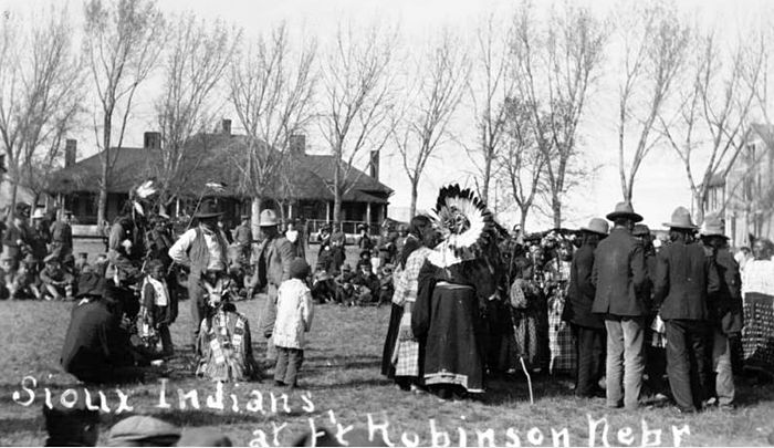 Sioux men, women, and children sit and stand near a group of trees at Fort Robinson, Nebraska. One man wears a feather headdress. Another man wears a beaded and fringed shirt. Two houses are in the distance.  [between 1874 and 1880?]