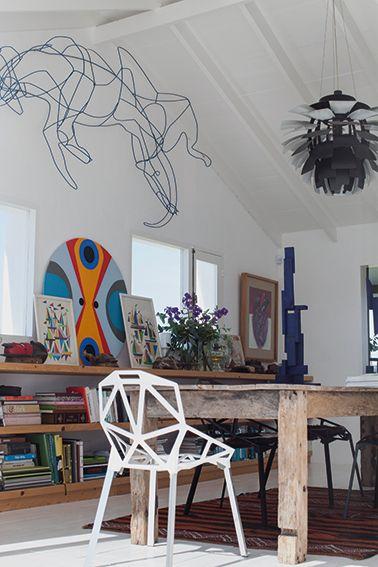 Contraste de estilos. Una alfombra artesanal convive con una biblioteca y obras de arte modernas. Para la mesa de madera rústica se eligieron las sillas de diseño Chair One de Konstantin. Foto de Jesús Guiarud
