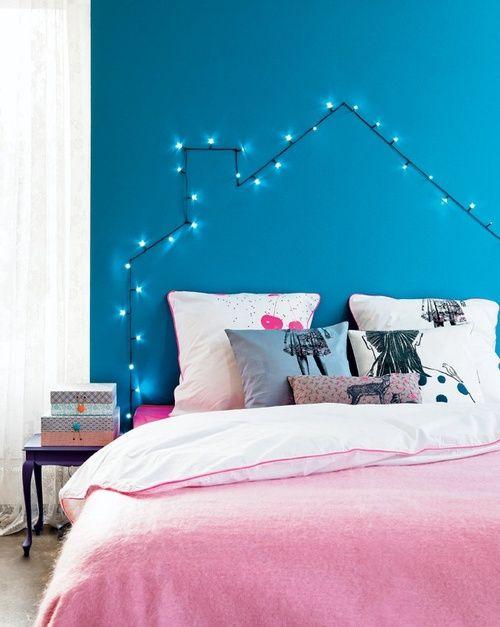 quarto decorado com luzes de natal, fairy lights. POarede Azul, roupa de cama rosa e criado mudo roxo