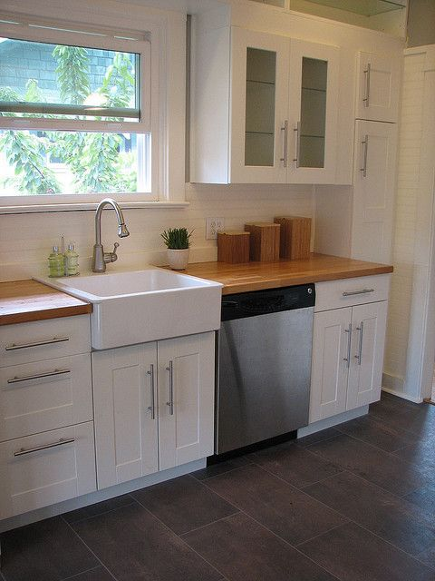 white cabinets, white farmhouse sink, bead board back splash, light butcher block counters & dark wood floors
