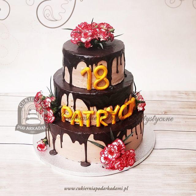 192BA Piętrowy tort oblany czekoladą i udekorowany goździkami.  3-tiered cake with chocolate icing, decorated with fresh flowers.