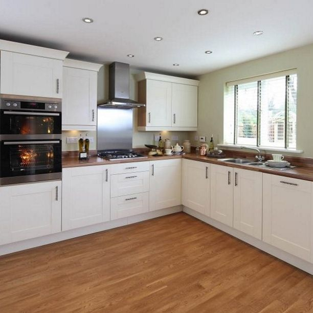 Wooden surface, cream cupboards, wooden floor and sage walls