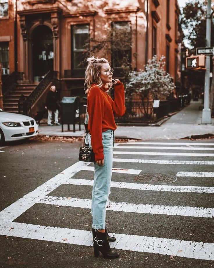 Casual Outfit Inspiration: frayed hem light wash high rise jeans, chunky black ankle boots, rust relaxed sweater, messy half bun