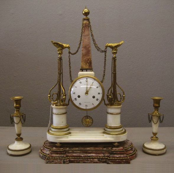 Fine Louis XV Ormulo and Mounted White Marble Mantel Clock & Candle Sticks. With Arabic numerals and pierced gilt hands, with Red Marble Base decorated with gilt beads. The sunburst pendulum is silk suspended. Circular enameled dial signed 'Orange A Versailles'. Both ends of the spring barrels are flanked by monuments topped with eagles, and a center Obelisk crowned with an orb and toupee feet.
