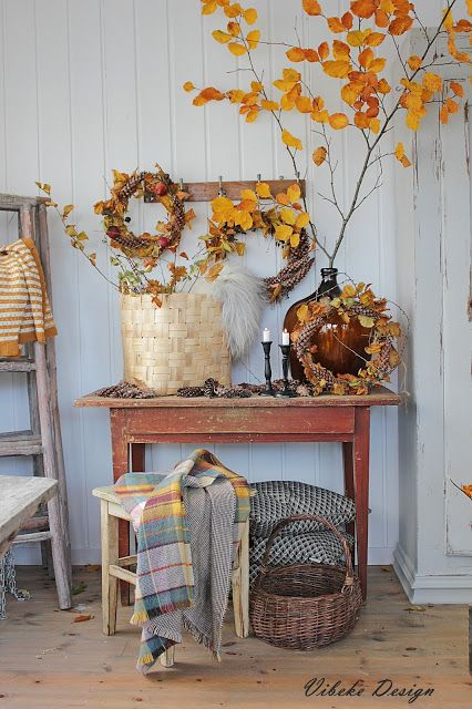 Such a lovely fall vignette!  I LOVE the pretty gold leaf branches, handmade pine cone wreaths, and warm textiles.
