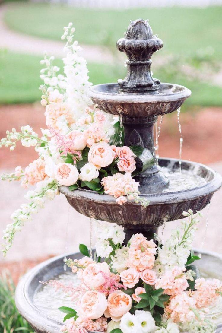 fontaine de jardin décorée de fleurs pour un mariage en plein air