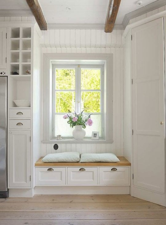 Love the window seat and built-in storage in this white bedroom.