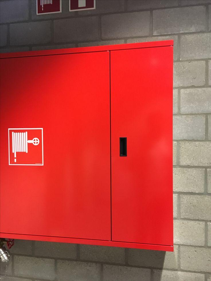 Lijn - De deur van de brandslang kast vormt zowel horizontaal als verticaal enkele lijnen die zo de omtrek van de deur duidelijk maken.