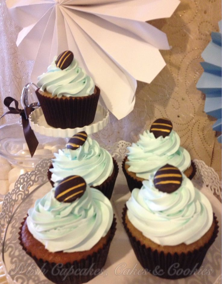 Banana spiced cupcakes topped with a blue vanilla butter cream swirl and gold painted chocolate, made by D'lish Cupcakes & Accessories