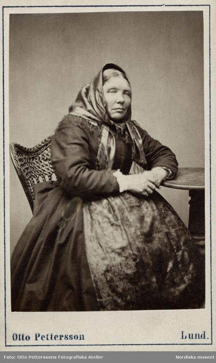 """Porträtt av kvinna iförd sjalett. Hon vilar ena armen på ett litet pelarbord. Vismarlöf, Bara hd. Gåfva af fotogr. O. Pettersson i Lund 73."""" . Nordiska museet inv.nr. 18518K."""