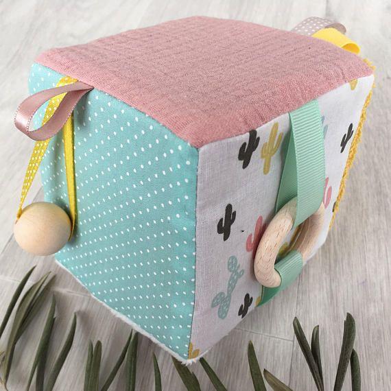 ✨Offrez à bébé un cube déveil pas comme les autres!!✨ Le cube éveille les sens de bébé grâce à ses différentes textures, au tintement de ses grelots cachés à lintérieur et à ses couleurs chatoyantes. Il soulage également bébé lors des poussées dentaires grâce a son anneau en