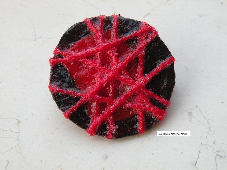 Riciclo creativo: spilla realizzata con un tappo di plastica squagliato, fili di lana e brillantini
