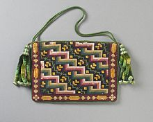 Woman's purse c. 1840. Cotton canvas with wool needlepoint, silk-braided cord, and silk chenille tassels, Europe. This is a style called Berlin wool work, based on printed patterns that were a predecessor to modern cross-stitch patterns.