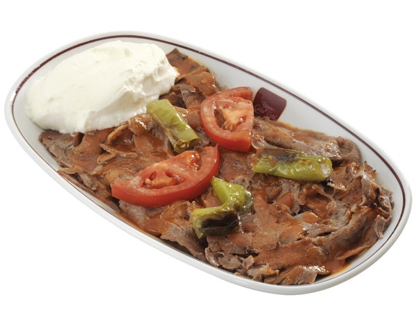 Iskender Kebab   2 lbs lamb (cubes)  4 onions (large)  1 teaspoon salt  1 teaspoon pepper  2 round pita breads  2 tablespoons tomato puree  2 large tomatoes  2 glasses plain yoghurt  4 cloves garlic  4 tablespoons butter  1 pinch cayenne pepper  4 chili peppers (large)  olive oil